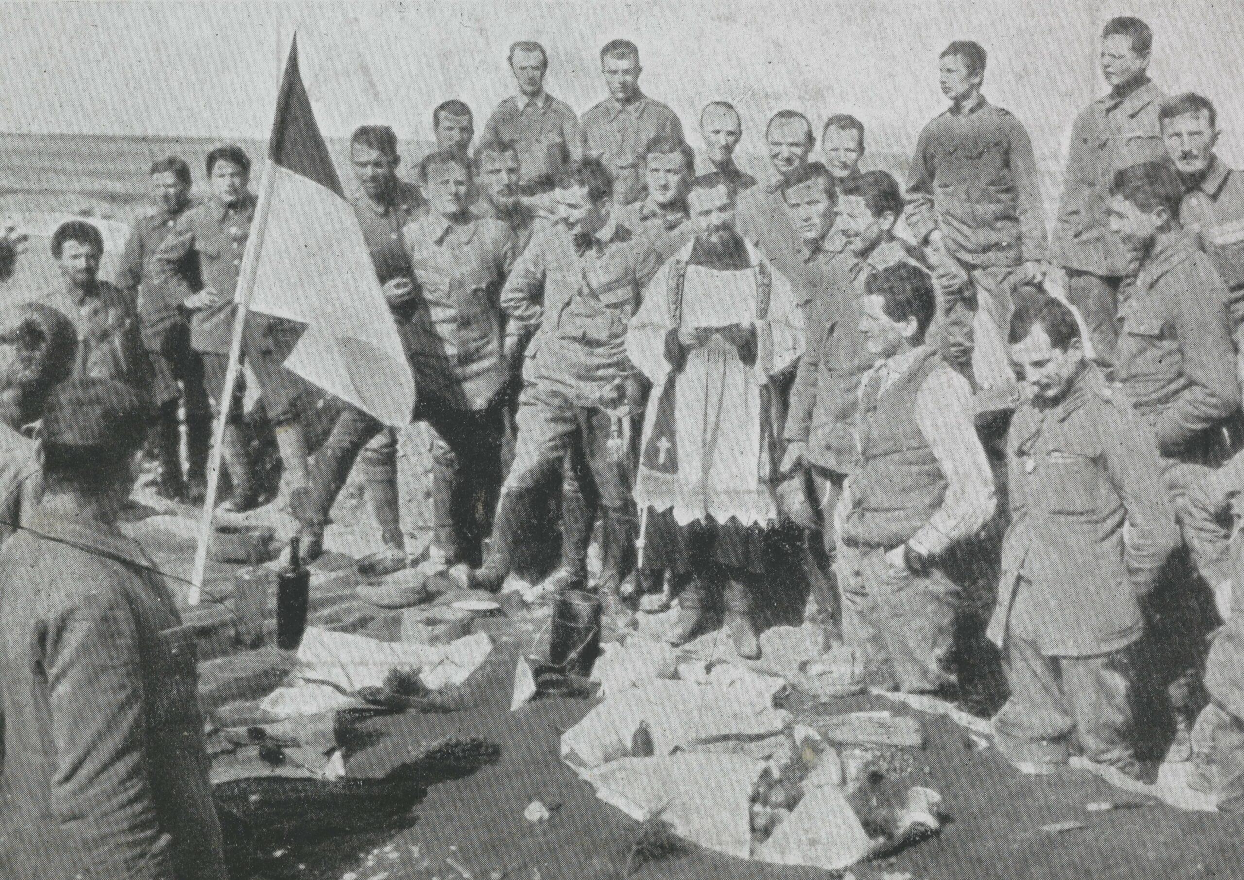 Żołnierze I Brygady Legionów Polskich stoją przy stole świątecznym. W centralnej części fotografii ksiądz.