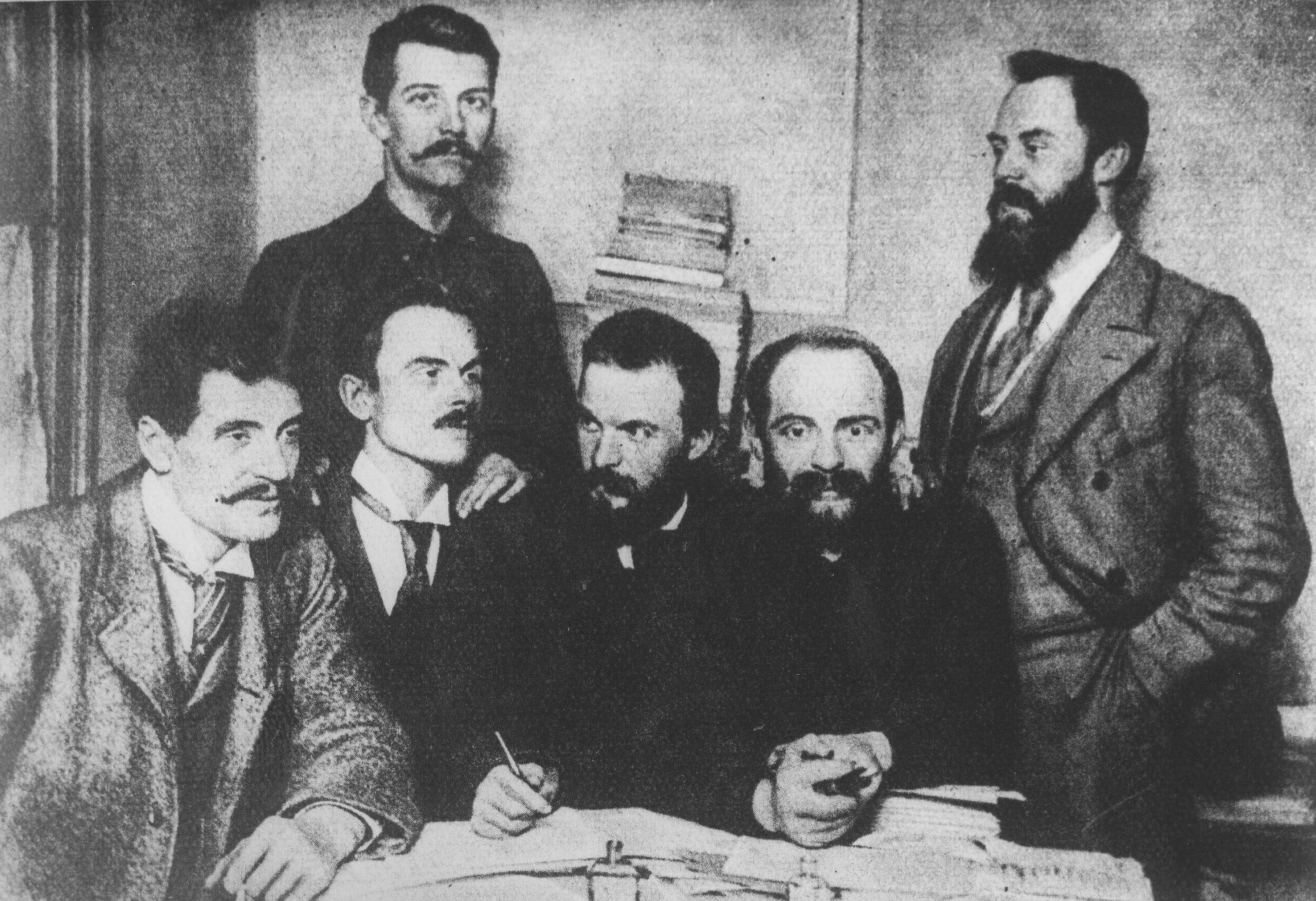 Przywódcy Polskiej Partii Socjalistycznej w Londynie. Mężczyźni znajdują się w pokoju przy stole, na którym leży duża ilość dokumentów. Siedzą od lewej: Ignacy Mościcki, Jędrzejewicz, Józef Piłsudski, Aleksander Dębski; stoją Bolesław Miklaszewski i Witold Jodko-Narkiewicz, 1896 r.