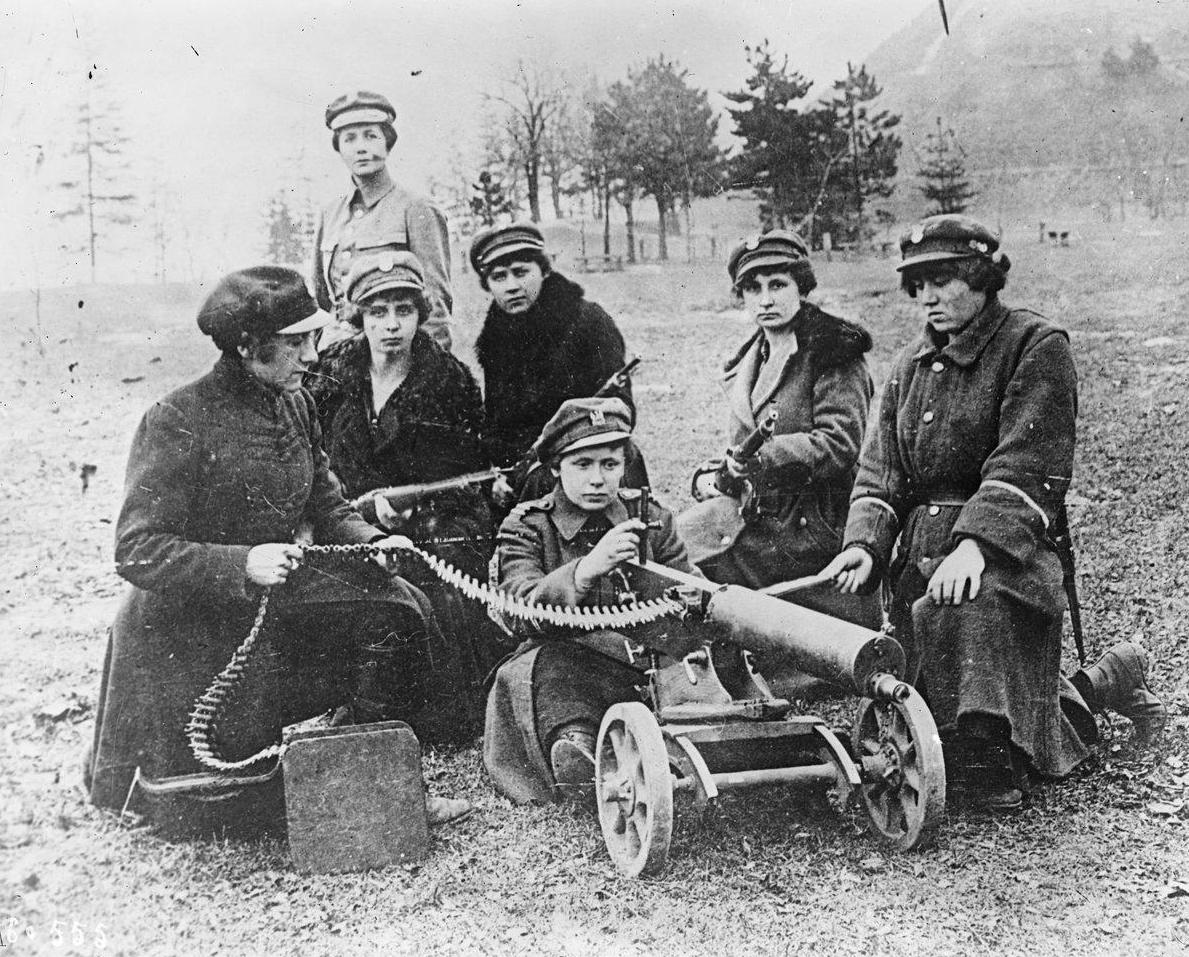 Kobiety w mundurach i płaszczach wojskowych przy ciężkim karabinie maszynowym. Na trzecim planie Aleksandra Zagórska