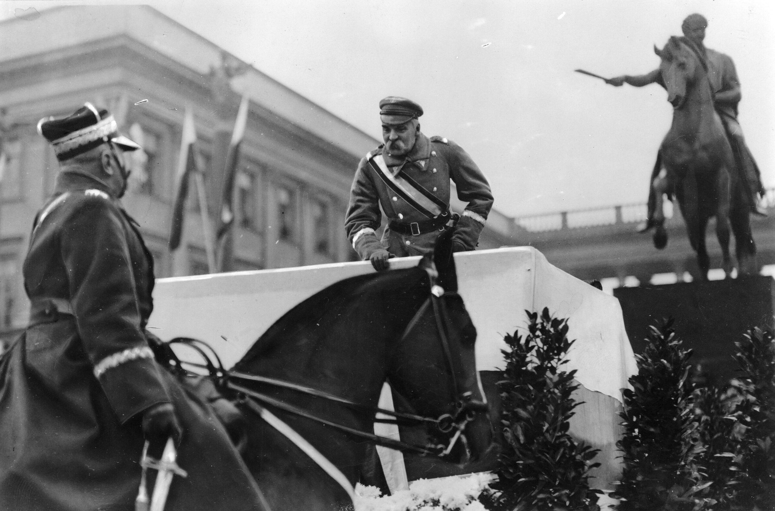 Józef Piłsudski pochyla się z podestu i zwraca do oficera na koniu. W tle pomnik konny Józefa Poniatowskiego.